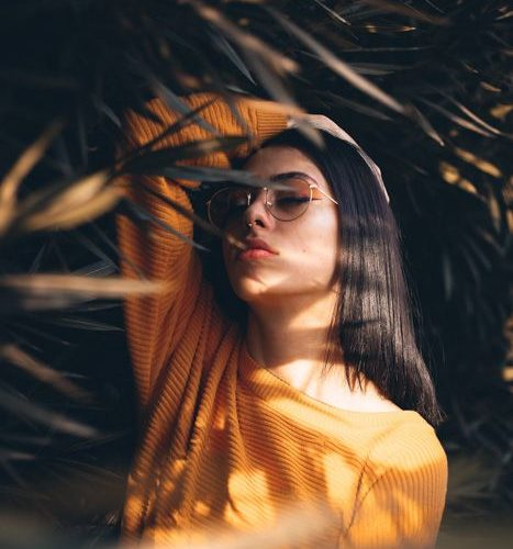 A portrait of a female model posing among foliage – best photography tutorials