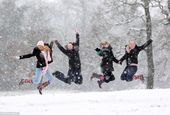 Teenage girls celebrate in the snow in their wellington boots after their school…